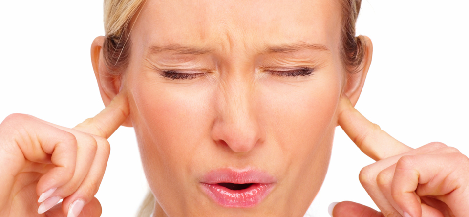 Frustrated young blond woman with fingers in ears
